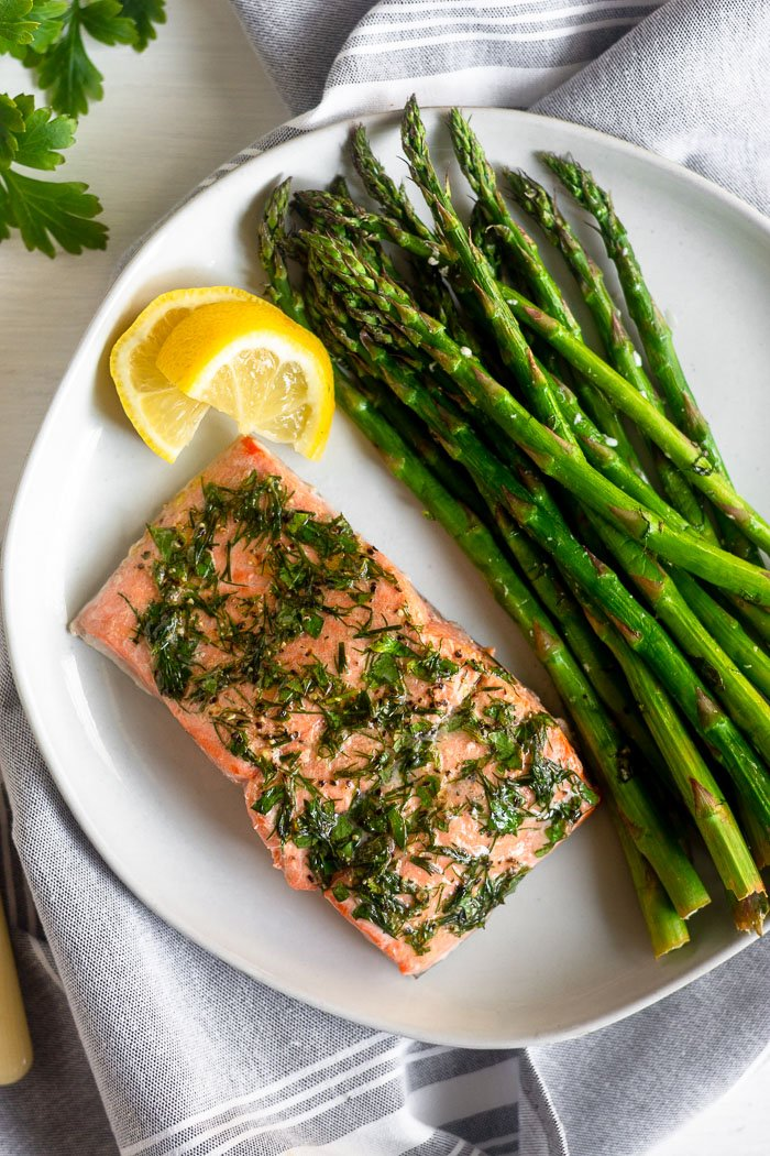 Dill coated salmon and asparagus on a white plate with two lemon wedges next too it. It is on a grey towel with fresh parsley next to it.