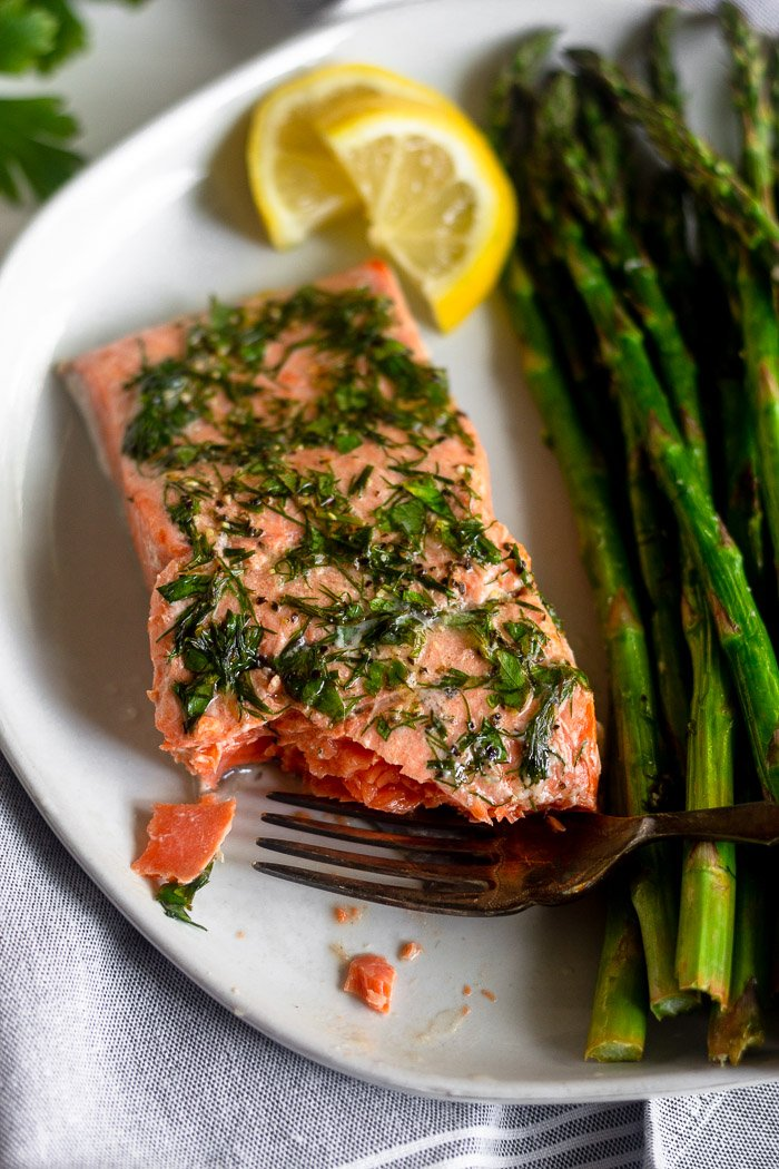 Air fryer salmon ans asparagus on a white plate. There is a bite out of the salmon with a fork resting on the plate.