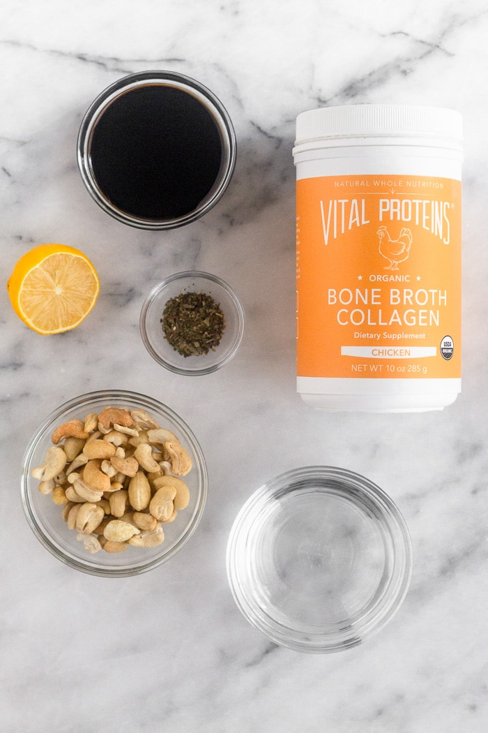 White marble counter filled with Vital Proteins bone broth collagen, water, balsamic vinegar, cashews, lemon, and dried basil.