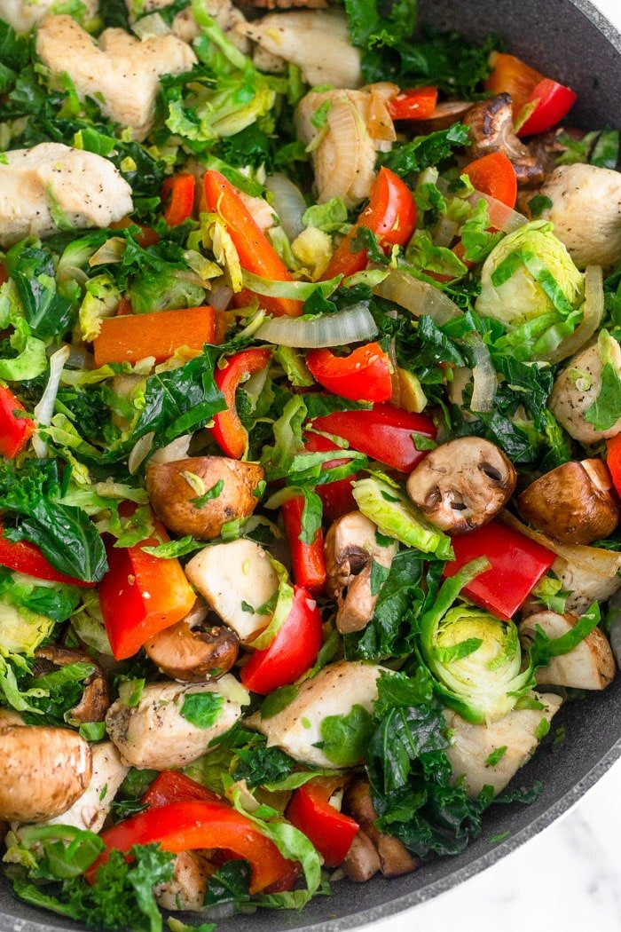 Large skillet filled with sautéed chicken and veggies.