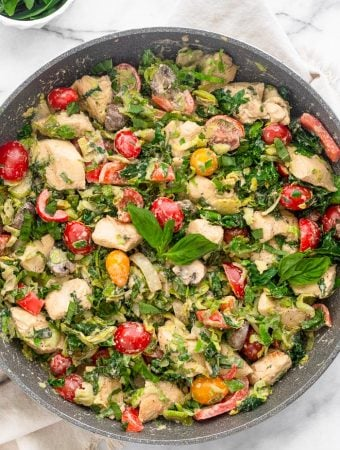 A pan filled with creamy balsamic chicken and veggies made in one pan and done in 30 minutes. It is topped with fresh basil and a small bowl of basil is next to it.