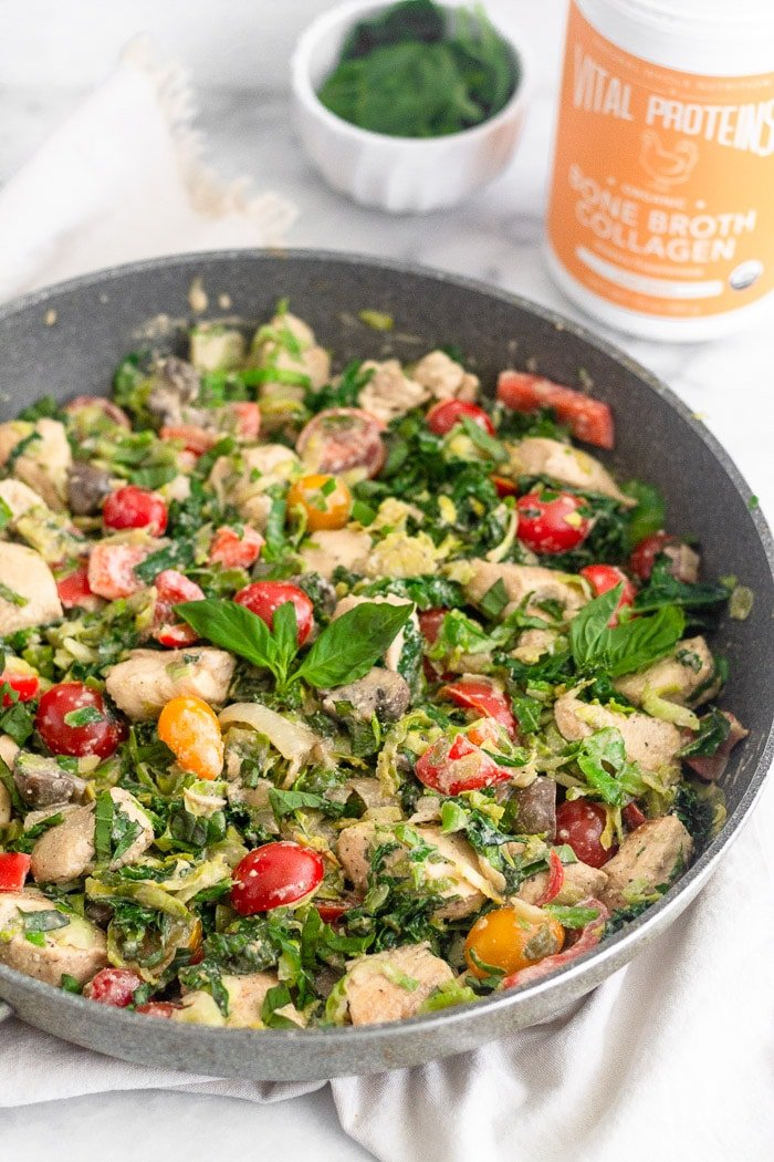 Large skillet filled with creamy balsamic chicken & veggies topped with fresh basil. Behind it is a container of Vital Proteins bone broth collagen and a small bowl of basil.