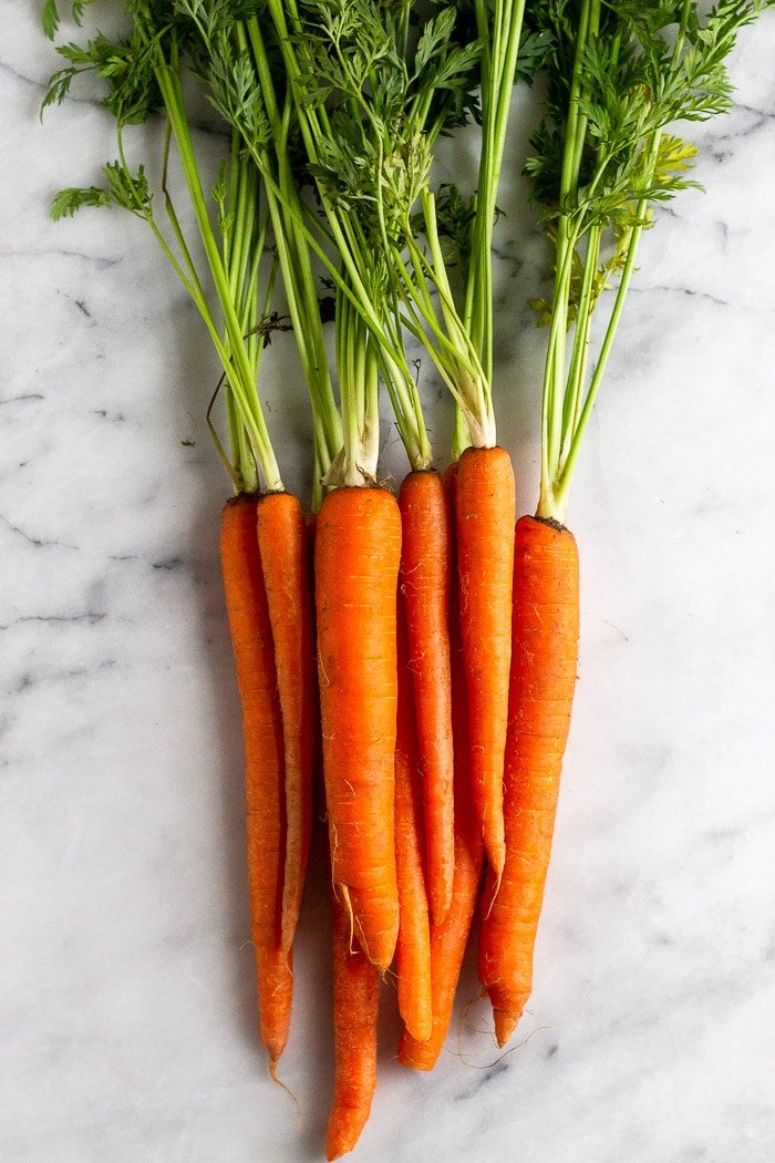 A bunch of fresh carrots with the tops on them.
