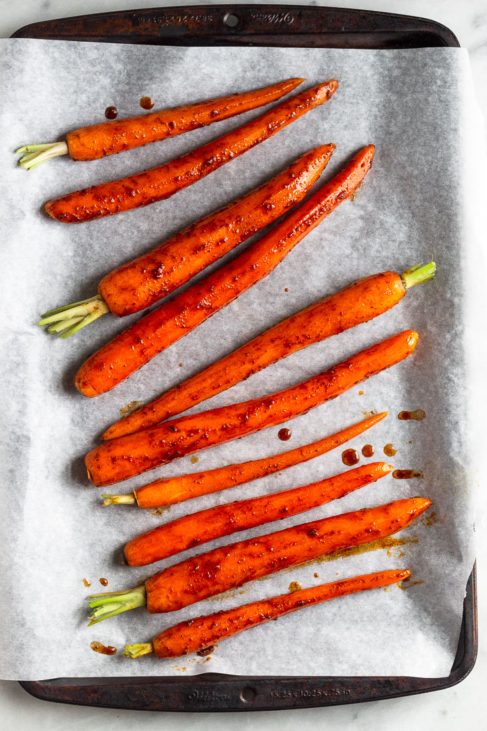 Overhead shot of glazed carrots on a baking sheet.