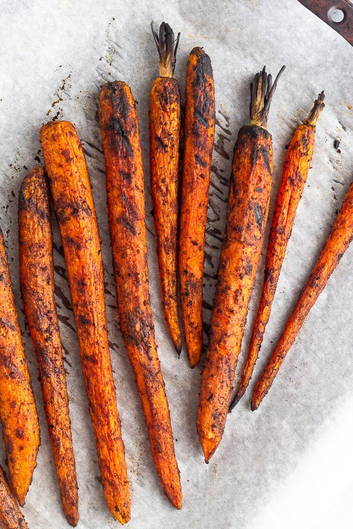A baking sheet lined with parchment paper and filled with roasted carrots on the grill.