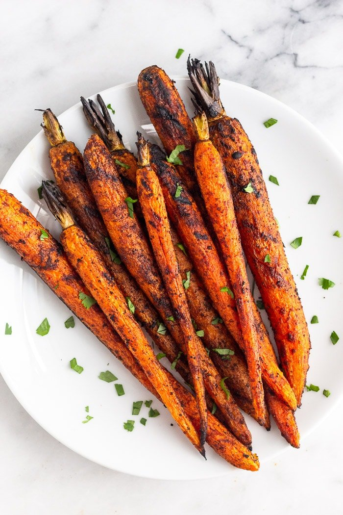 Overhead shot of grilled carrots on a plate topped with fresh herbs.