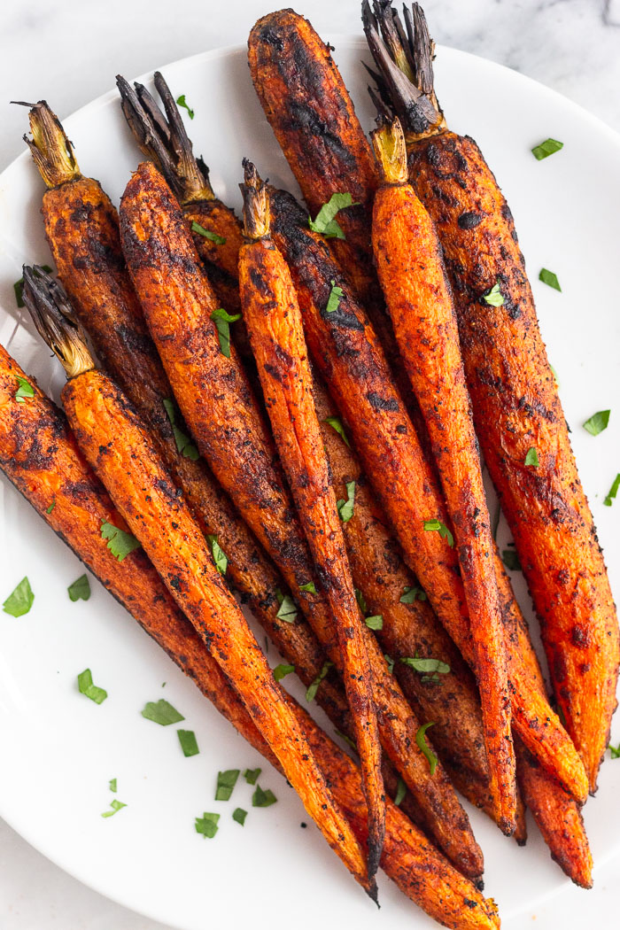 Close up of a white plate with glazed grilled carrots topped with freshly chopped herbs.