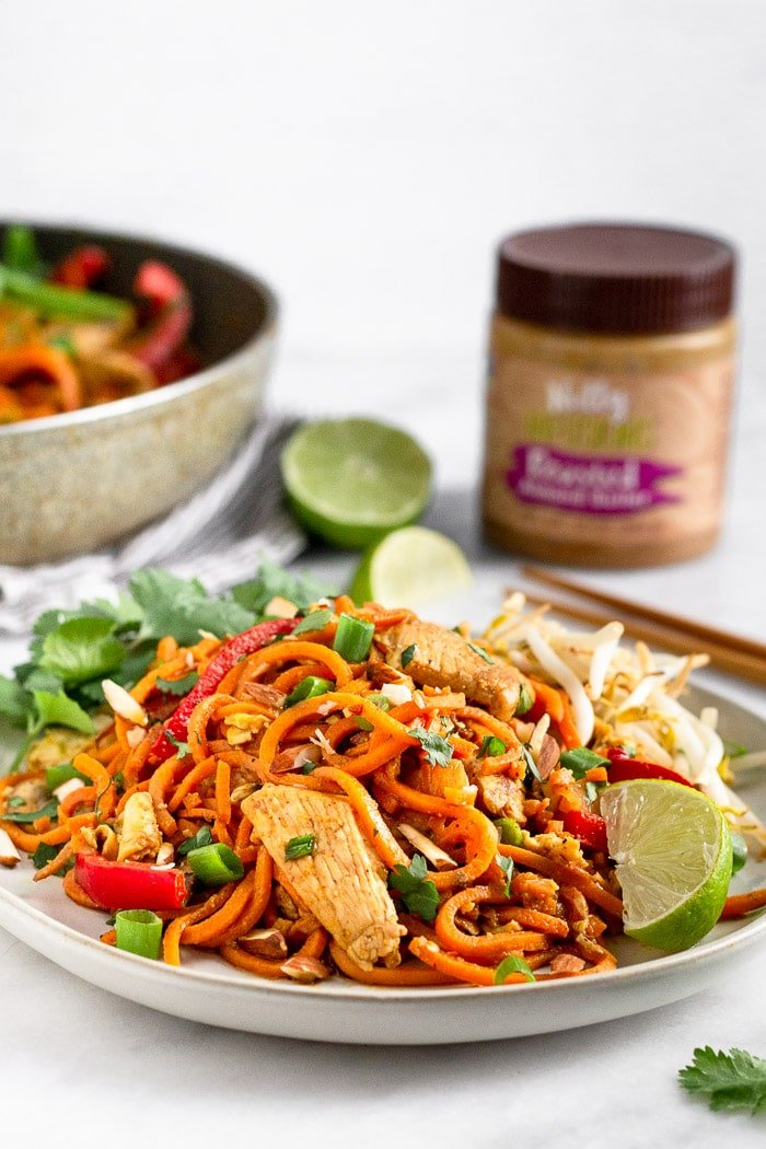Plate of healthy chicken pad topped the cilantro, lime wedges, and bean sprouts. Behind it is a jar of almond butter, skillet of more paleo pad Thai, and limes.