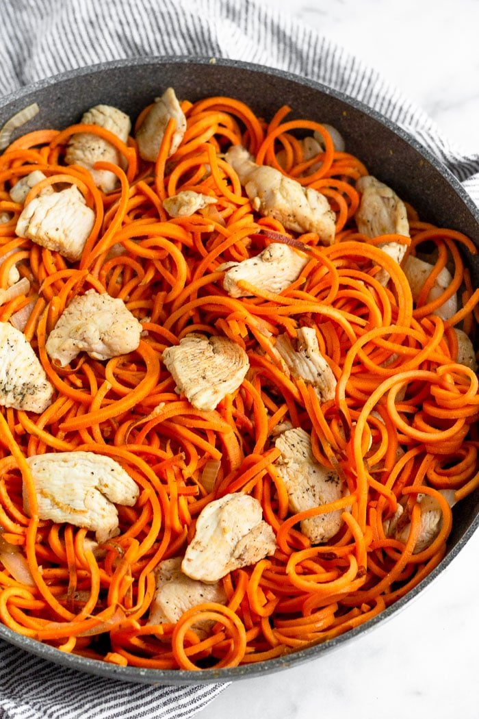 Large saute pan filled with sweet potato noodles and cooked chicken breast for sweet potato Pad Thai.