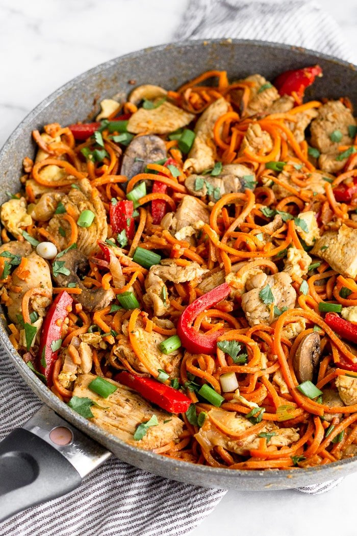 Large sauté pan filled with healthy chicken pad Thai that uses sweet potato noodles.