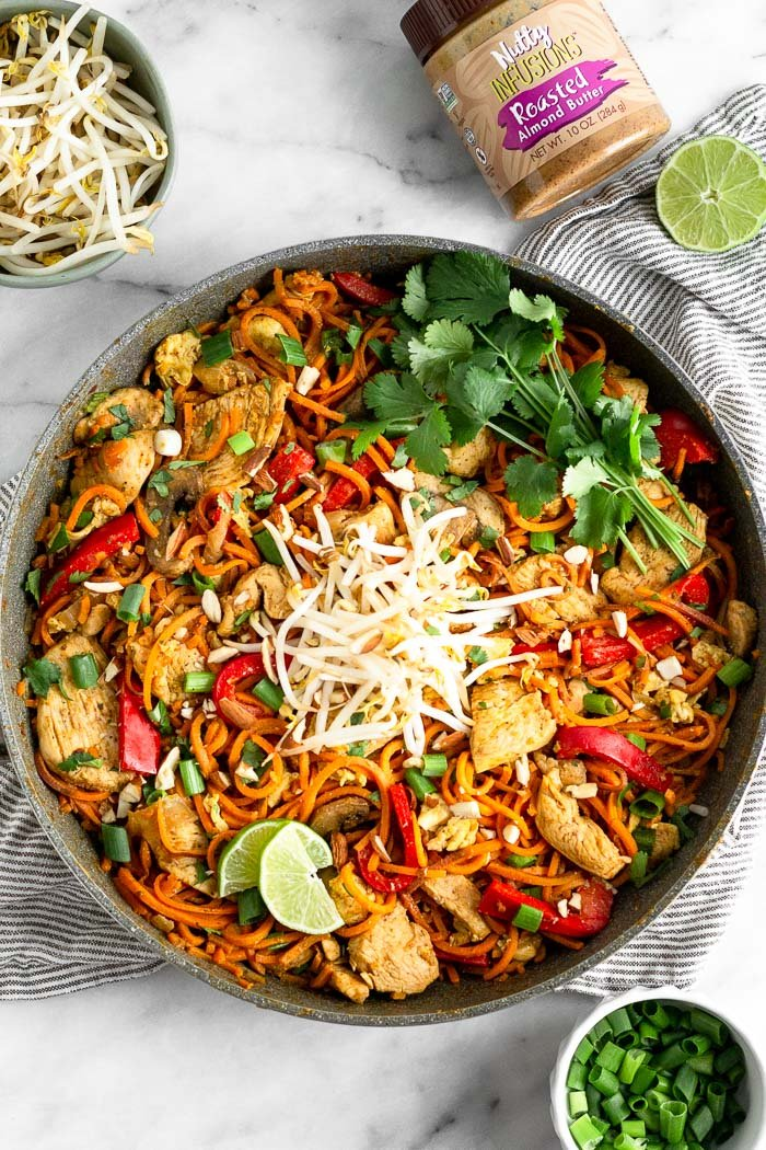 Large skillet filled with sweet potato healthy chicken pad Thai topped with bean sprout, cilantro, and lime wedges. Next to it is a small bowl of green onions, bowl of bean sprouts, half a lime wedge, and a jar of almond butter.