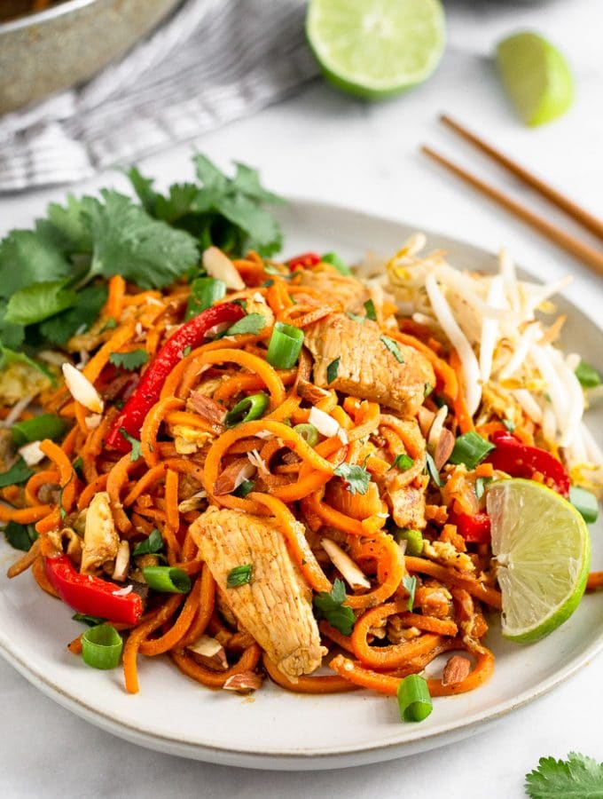 White plate filled with sweet potato chicken pad Thai garnished with lime wedges, bean sprouts, and cilantro.