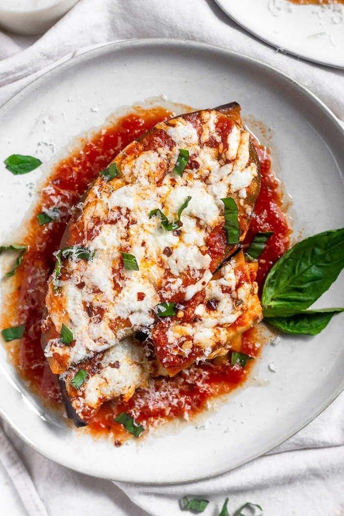 Overhead view of not breaded instant pot eggplant parmesan topped with fresh basil, parmesan cheese, and red pepper flakes.