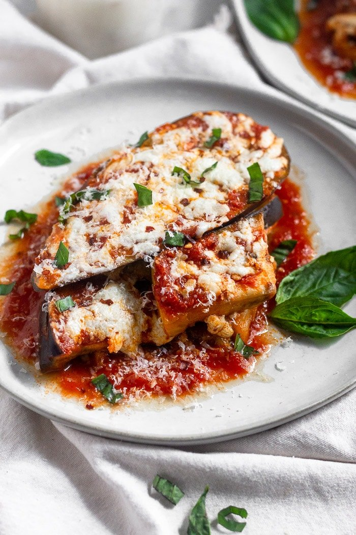 Healthy Instant Pot eggplant parmesan topped with fresh basil, red pepper flakes, and mozzarella cheese on a white that is sitting on a white linen.