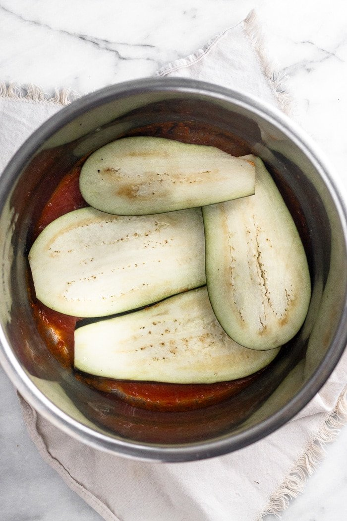 Instant Pot filled with a layer of sauce on the bottom and then topped with a slices of eggplant covering the bottom.