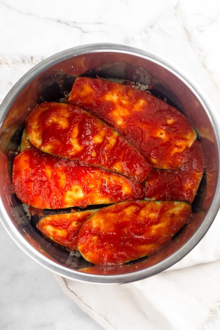 Layers of healthy eggplant parmesan in an Instant Pot covered with a layer of marinara sauce.