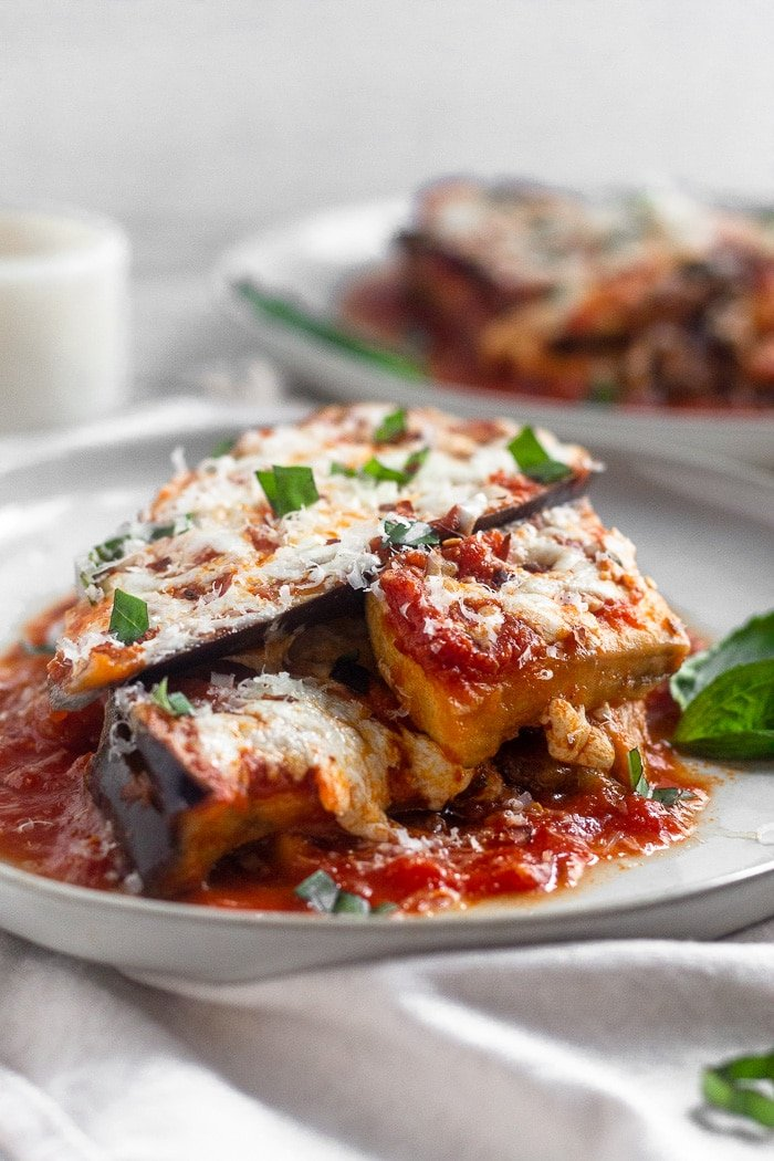 Layers of instant pot eggplant parmesan topped with fresh basil sitting on a white plate. There is another plate behind it with more healthy eggplant parmesan on it.