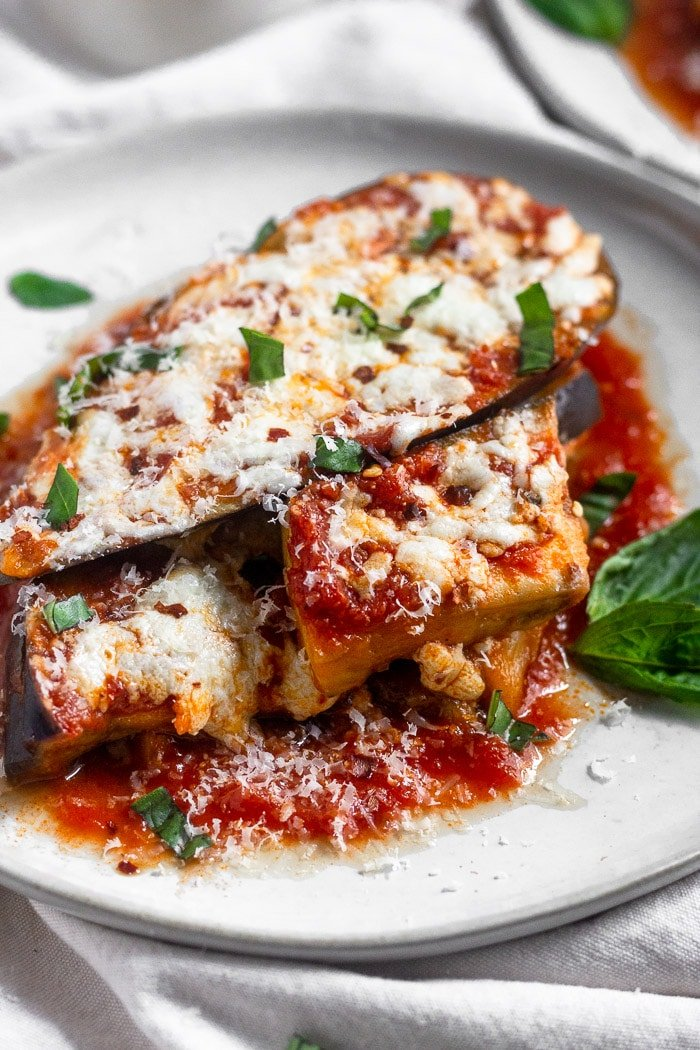 Healthy instant pot eggplant parmesan without breadcrumbs topped with fresh basil, parmesan cheese, and red pepper flakes.