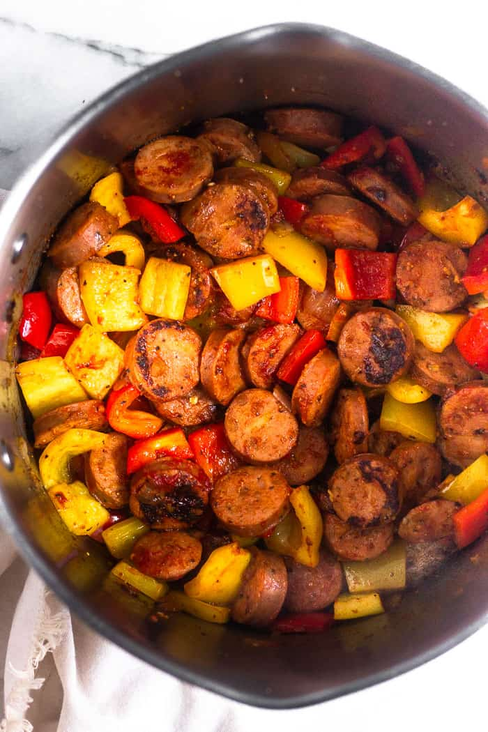 Large stock pot filled with sautéed peppers, onion, and sausage. The pot is sitting on a tan linen.