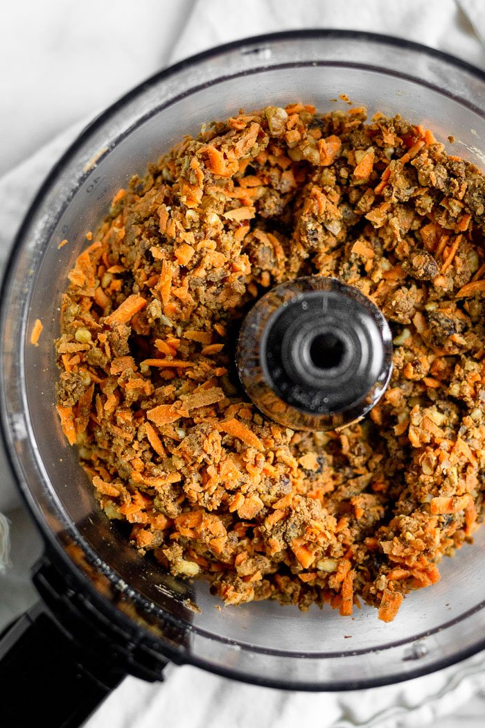 A food processor filled with the batter for no bake carrot cake protein bars. The batter consists of dates, raisins, walnuts, carrots, protein powder, and spices.