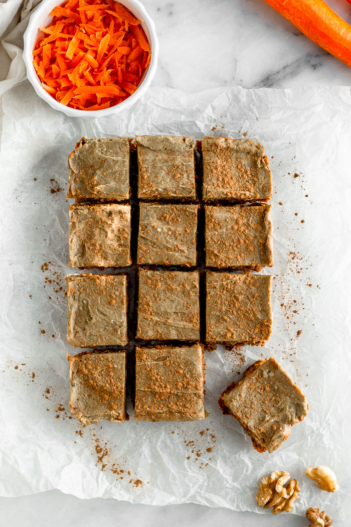 Overhead shot of vegan carrot cake protein bars that are cut into 12 squares. Ones of the square is pulled away from the others. Surrounded them are walnuts and carrots.