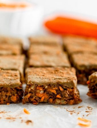 Rows of no bake carrot cake protein cars topped with protein icing and cinnamon. Behind them are large carrots and bowl of shredded carrots.
