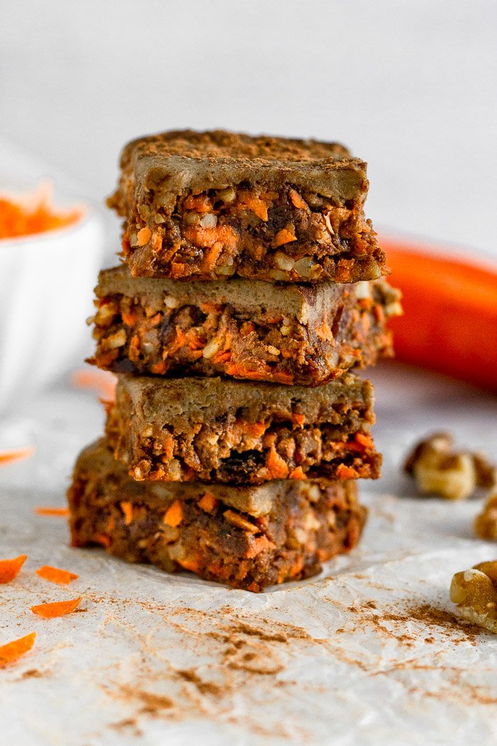 4 vegan no bake carrot cake protein bars stacked on top of each other. Around them are walnuts, carrots, and shredded carrots.