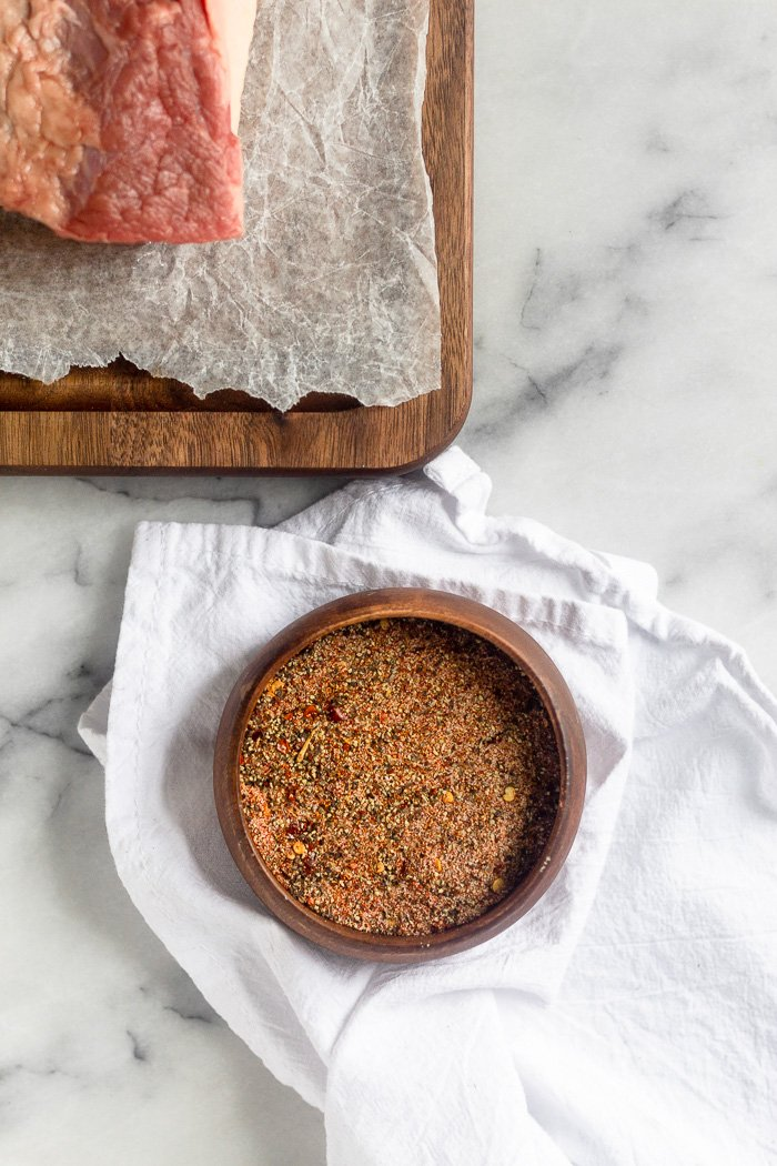 Small bowl of dry rub spices. It is sitting on a white towel with a brisket on a cutting board next to it.