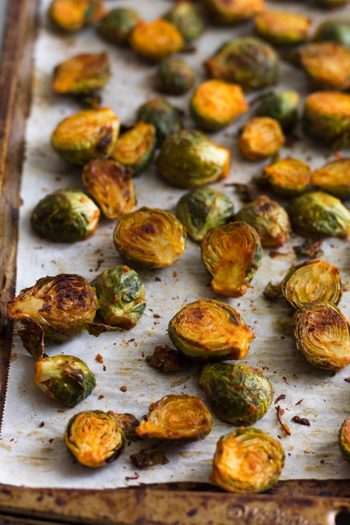 Baking sheet filled with roasted buffalo Brussels sprouts,