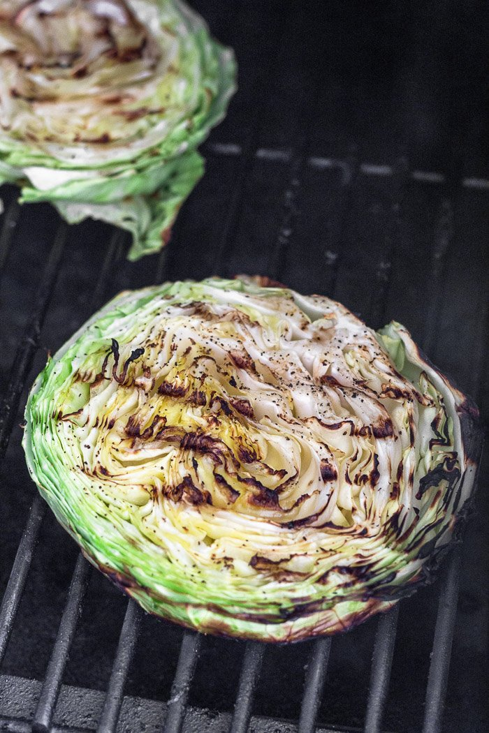 A grilled cabbage steak with grill marks on it sitting on the grill.
