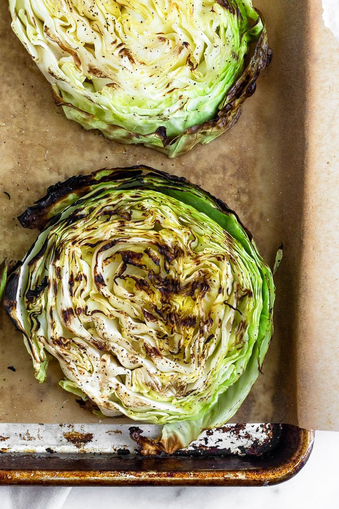 Close up of a grilled cabbage steak with grill marks on it. It is sitting on a baking sheet with other cabbage steaks,