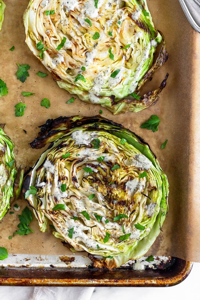 Baking sheet with grilled cabbage steaks on it drizzled in ranch and topped with fresh herbs.