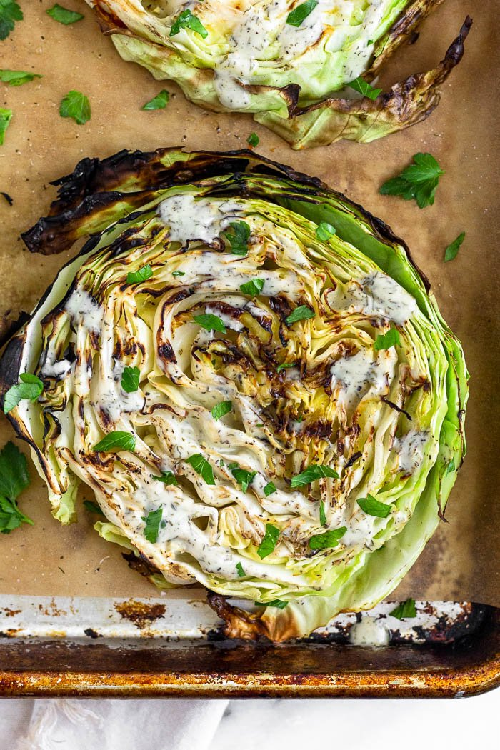 Grilled cabbage steak on a baking sheet drizzled in ranch dressing and topped with fresh parsley.