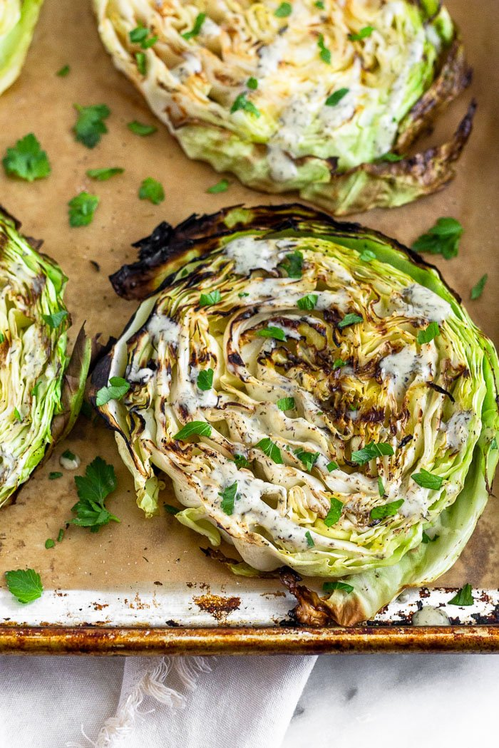 Grilled cabbage steaks on a baking sheet drizzled with ranch and garnished with fresh herbs.