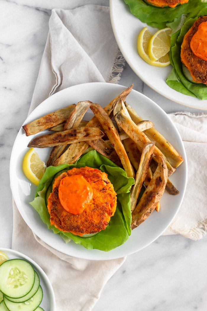 Harissa salmon burger on a lettuce leaf topped with harissa aioli and sweet potato fries on a white plate. It is sitting on tan linen and around it is a plate of sliced cucumbers and another plate of salmon burgers.