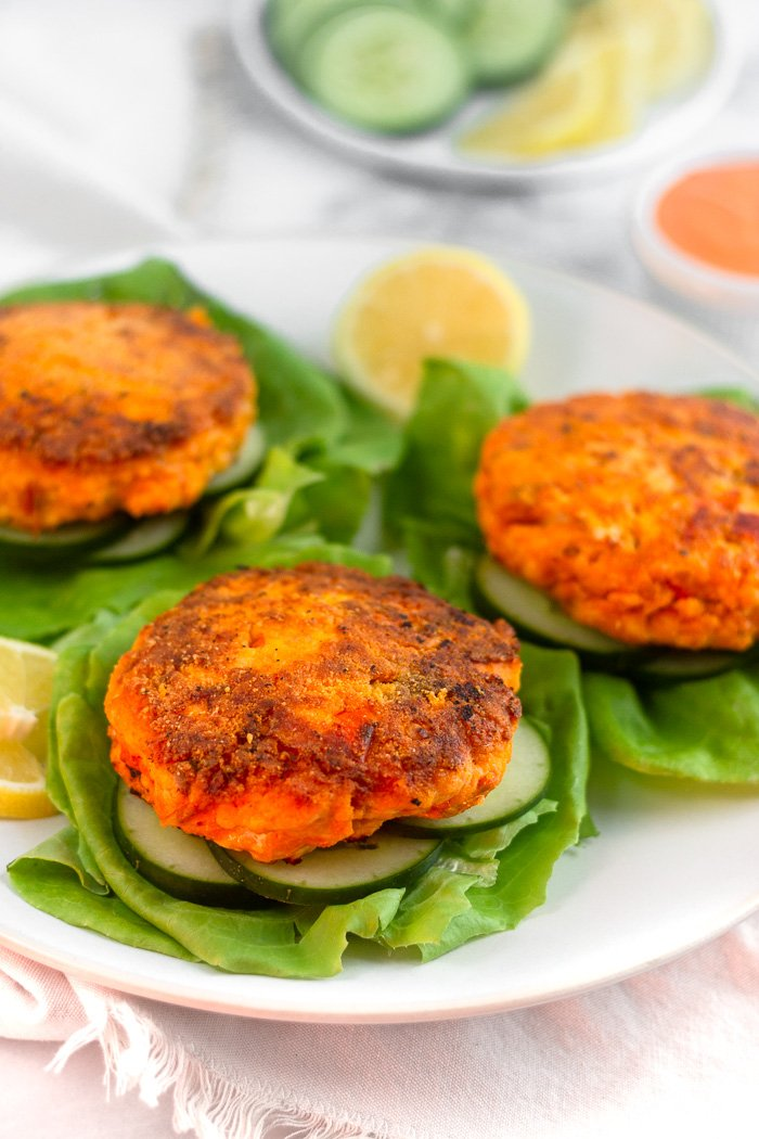 Plate of harissa salmon burgers on sliced cucumbers on lettuce leaves. Behind them is a plate of cucumbers and lemons and a bowl of harissa aioli.