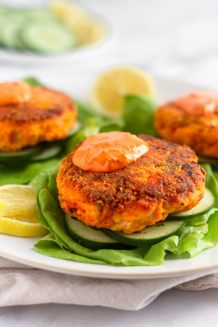Harissa salmon burger topped with harissa aioli sitting on a sliced cucumbers on a lettuce leaf. Behind it is more salmon burgers on the plate.