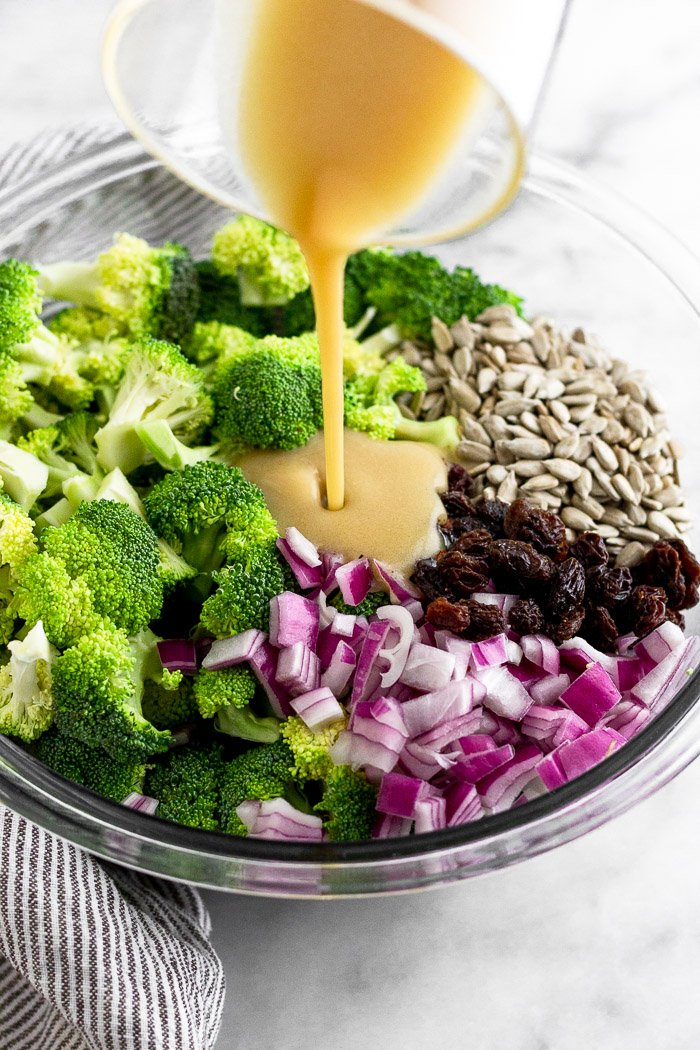 Homemade honey mustard being poured overtop broccoli raisin salad before it is mixed up.