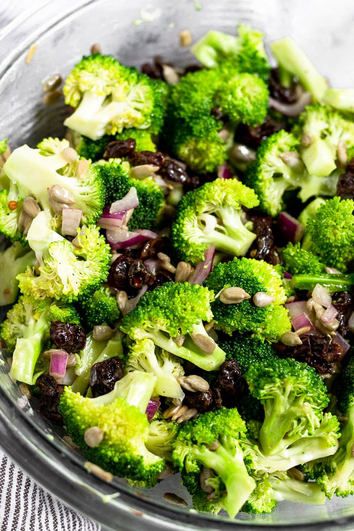 Close up of a glass bowl of healthy broccoli salad.