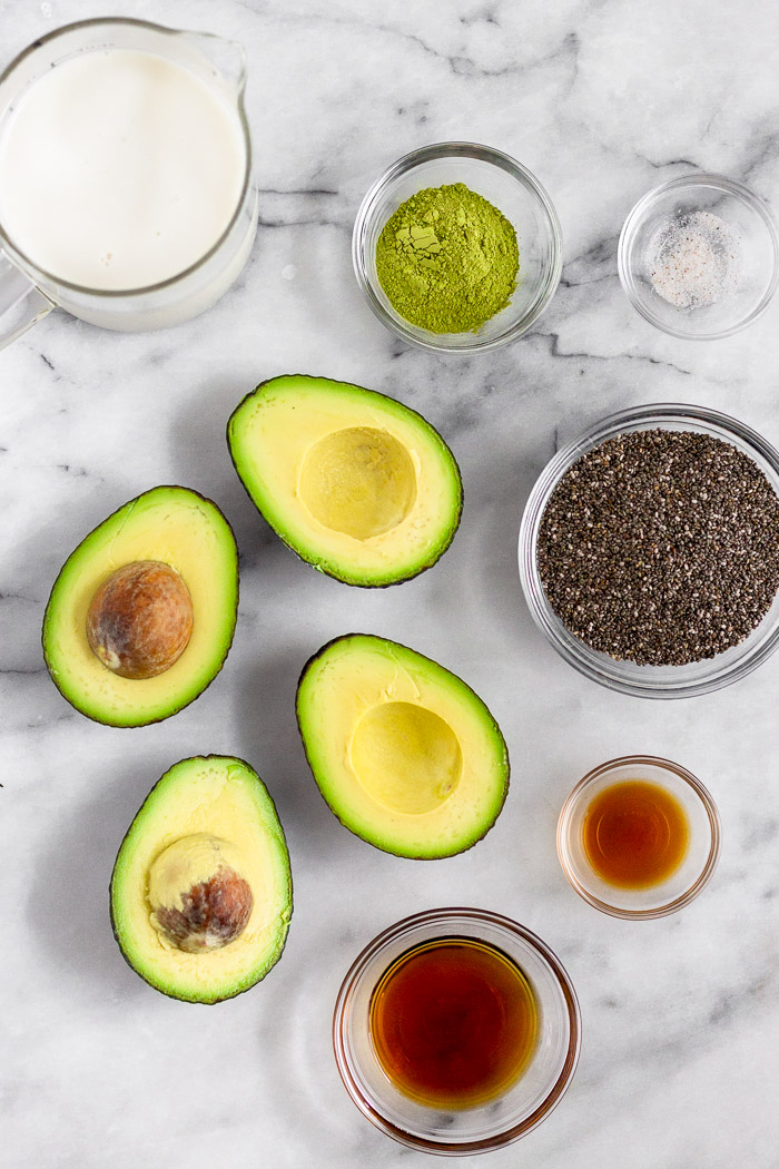 Avocados cut in half, pitcher of nut milk, and bowls of matcha powder, salt, chia seeds, vanilla extract, and maple syrup on a marble counter top.