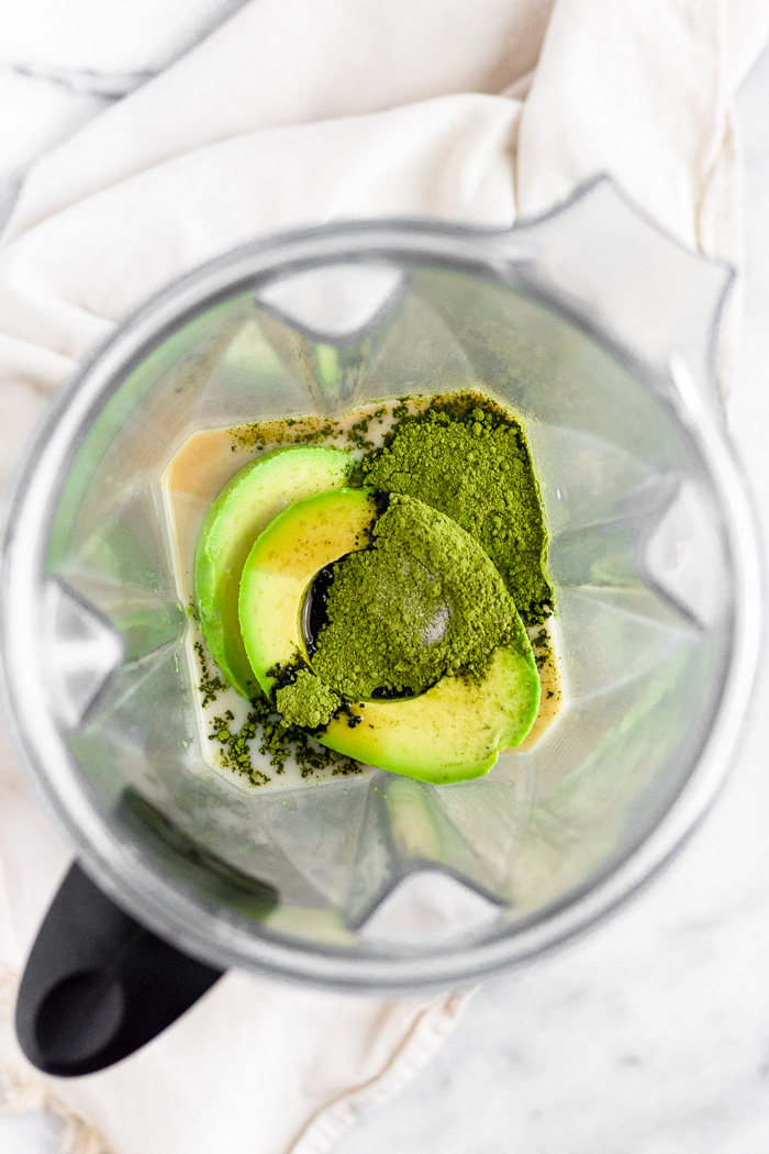 A blender filled with nut milk, avocados, maple syrup, vanilla extract, matcha, and salt.