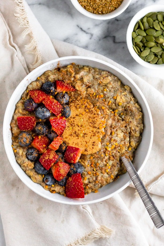 Bowl of oatmeal with seed cycling seeds mixed in. It is topped with cashew butter, fresh berries, and bee pollen. Bowl is sitting on a tan towel and next to two small bowls filled with pumpkin and flax seeds.