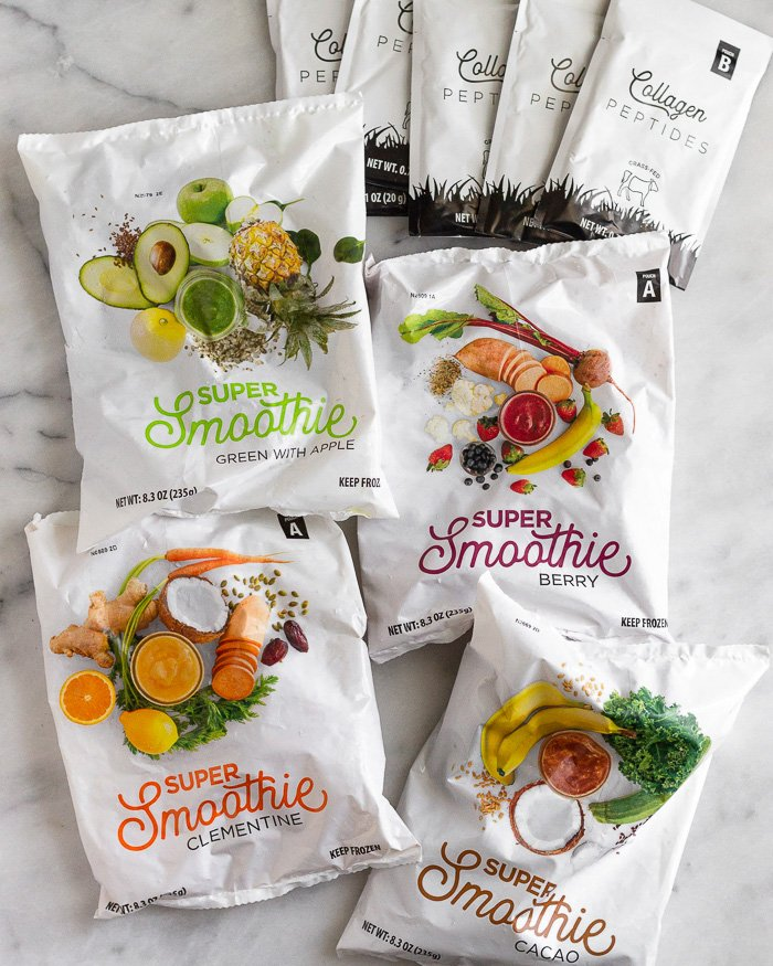 Four packs of Smoothie Box flavors along with 4 packets of collagen on a white counter top.