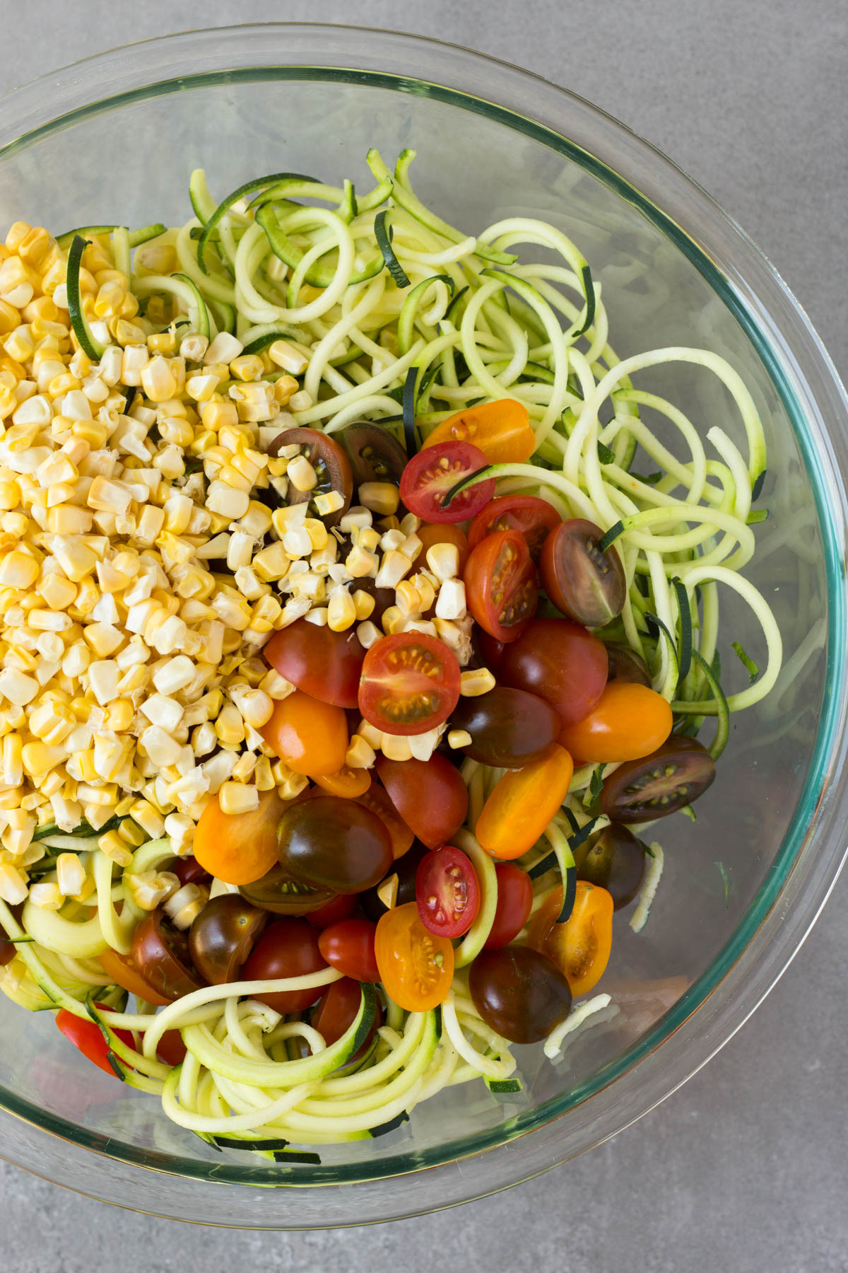Large glass bowl filled with zucchini noodles, corn, and halved cherry tomatoes.