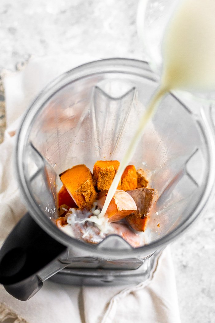 Blender filled with frozen sweet potato and other sweet potato smoothie ingredients with almond milk being poured into it.