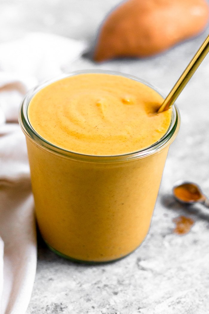Jar filled with sweet potato smoothie with a sweet potato behind it. Next to it is a teaspoon of cinnamon and a tan linen.