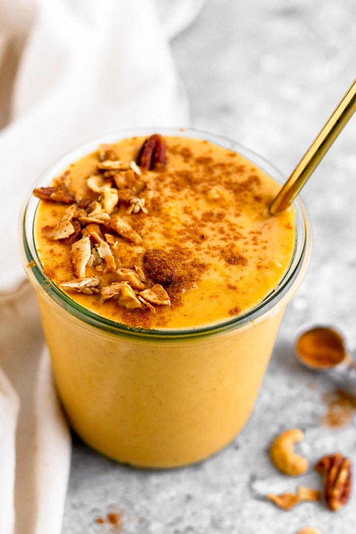 Healthy sweet potato smoothie topped with cinnamon and granola with a straw coming out of it. Next to it is more granola and a teaspoon of cinnamon.