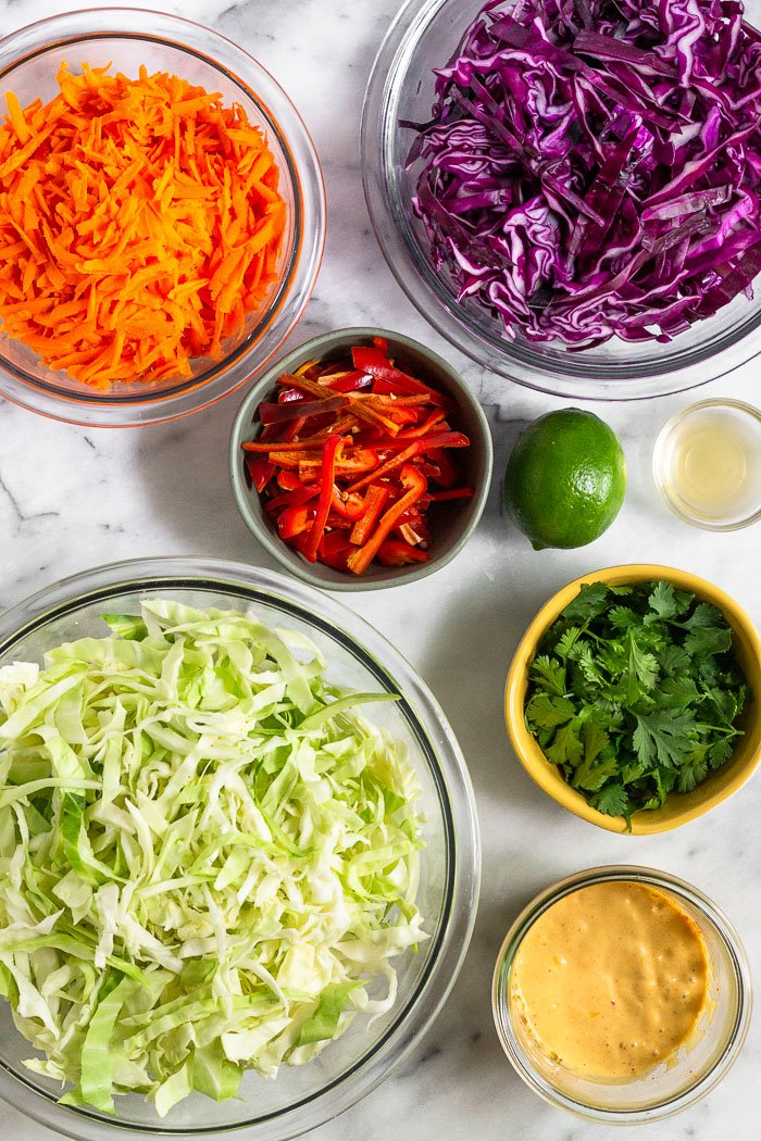 Different bowls filled with carrots, shredded purple cabbage, red peppers, cilantro, green cabbage, chipotle mayo, apple cider vinegar, and a lime.