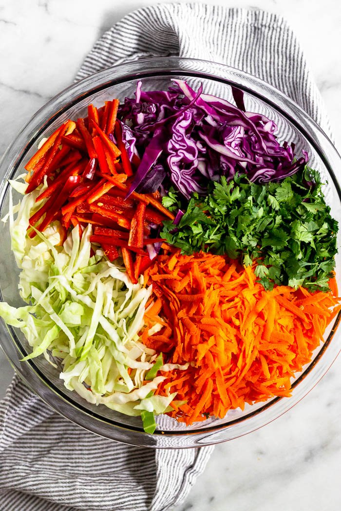 Large glass bowl filled with shredded cabbage, cilantro, shredded carrots, and sliced red pepper.