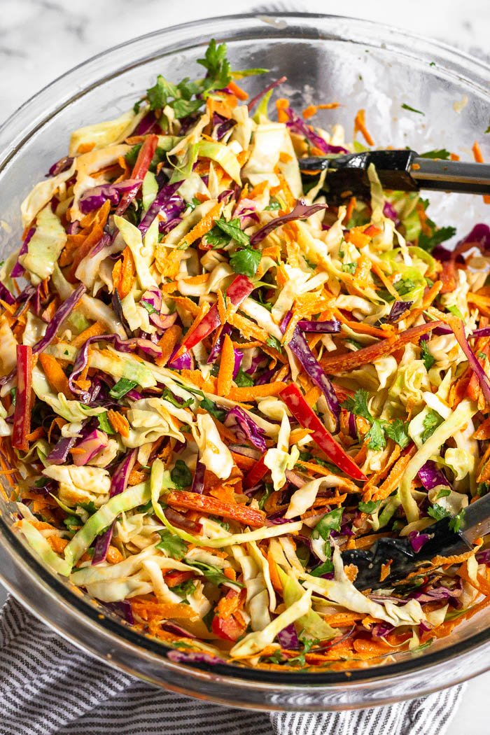 A bowl of Mexican coleslaw with tongs resting in it.